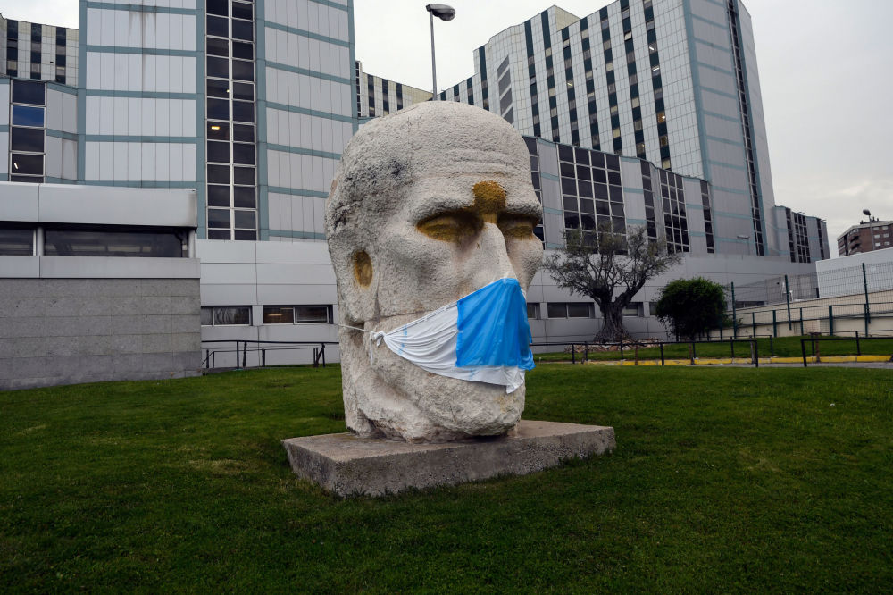 A face mask is placed on the statue of Spanish neuroscientist Santiago Ramon y Cajal by sculptor Eduardo Carretero outside the Ramon y Cajal Hospital in Madrid on April 14, 2020. - Spain's death toll from the novel coronavirus topped 18,000, as the rise in new infections dropped to its lowest level since the country imposed a nationwide lockdown last month.