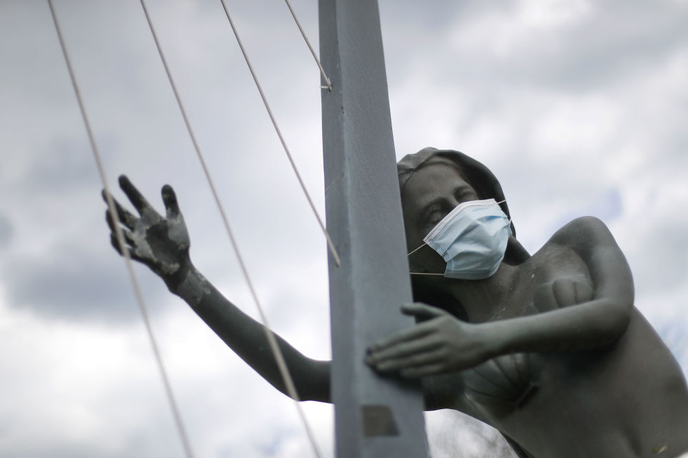 A protective mask is shown on a statue of a mermaid playing harp in St. Clair Shores, Mich., Thursday, May 7, 2020. Michigan Gov. Gretchen Whitmer said Thursday that auto and other manufacturing workers can return to the job next week, further easing her stay-at-home order while extending it through May 28 because of the new coronavirus COVID-19 pandemic.