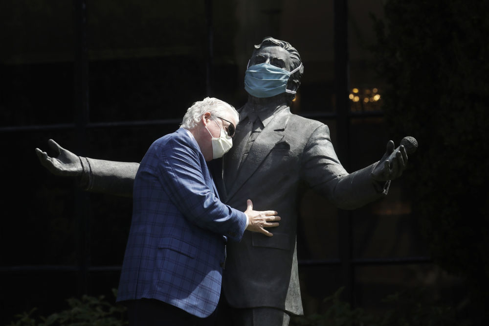 Paul Tormey, Regional Vice President of Fairmont Hotels, wears a mask while hugging a statue of singer Tony Bennett outside of the Fairmont San Francisco hotel before leading hotel workers in a singing of the song I Left My Heart in San Francisco, Saturday, April 25, 2020, in San Francisco. Bennett had encouraged San Franciscans to join him in a sing-a-long from their homes during shelter in place orders for COVID-19 concerns.