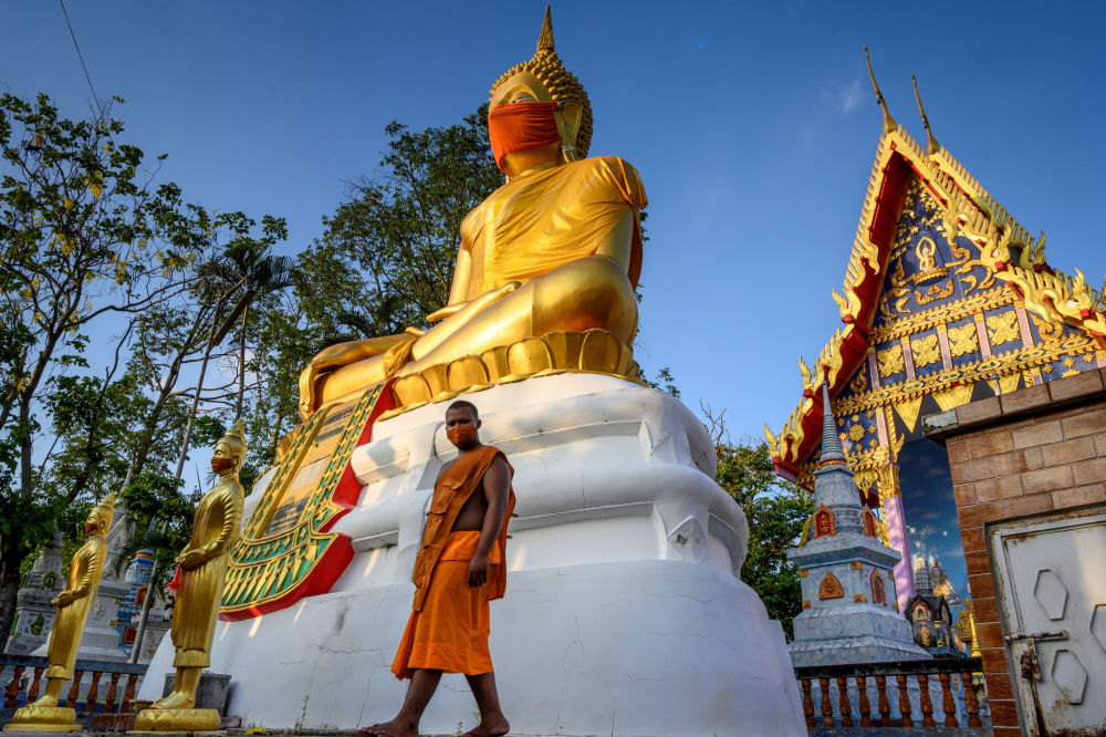 A monk walks in front of a giant Buddha statue wearing a face mask at Wat Nithet Rat Pradit temple in Pathum Thani outside Bangkok on May 12, 2020, as the country deals with the COVID-19 novel coronavirus situation.
