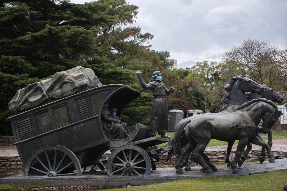A statue of a gaucho  family wearing face masks as if to prevent the spread of new coronavirus stands in Montevideo, Uruguay, Monday, May 4, 2020. The sculpture is part of a larger set which represents the pioneers in Uruguay and is called The Stage Coach. It was created by Uruguayan sculptor Jose Belloni in 1922.