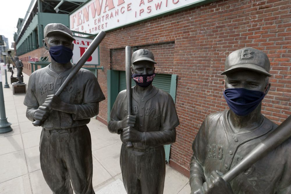 Statues of former Boston Red Sox greats, from left, Ted Williams, Bobby Doerr and Johnny Pesky, wear protective masks outside Fenway Park, Friday, April 17, 2020, in Boston.