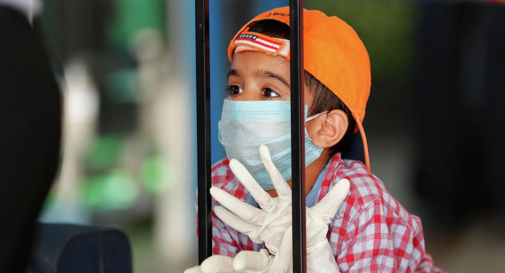 Ребенок в защитной маске и перчатках опирается на чемодан в ожидании рейса