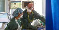 Врачи в защитных костюмах в палате интенсивной терапии в больнице с коронавирусом