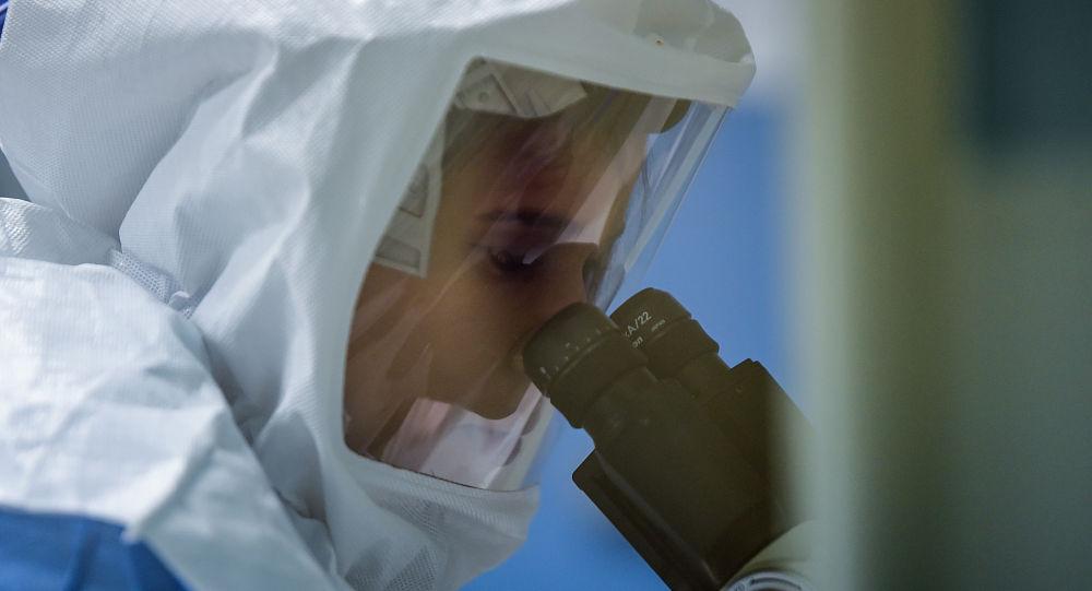 Сотрудник лаборатории в защитном костюме изучает образцы коронавируса под микроскопом