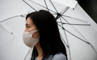 Девушка в маске гуляет на улице под зонтом