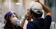 Сотрудник торгового центра в маске измеряет температуру у посетителя