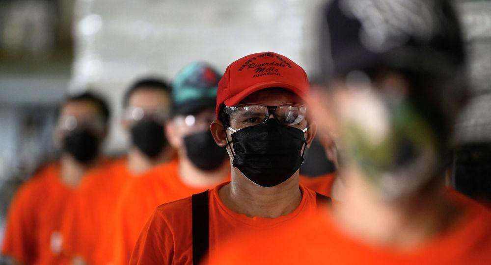 Молодые люди в защитных масках и очках выстроились перед входом в здание