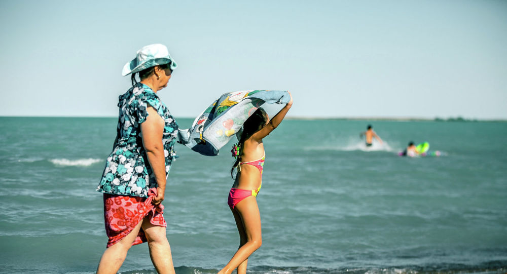 Бабушка с внучкой гуляют по пляжу озера Щучинско-Боровской курортной зоны