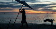 Человек убирает зонт на пляже в лучах заката