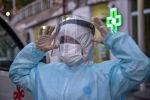 Врач в защитном костюме и перчатках поправляет лицевую маску у больницы с коронавирусом