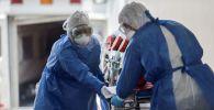 Врачи в защитных костюмах везут тяжелобольного в изоляционном боксе в палату интенсивной терапии в больнице с коронавирусом