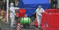 Сотрудники коммунальных служб проводят дезинфекцию территории вокруг рынка морепродуктов Хунань в китайском Ухане