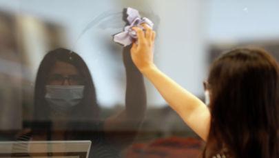 Девушка в маске протирает стекло в кафе после ослабления карантина