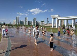 Астанчане освежаются в фонтане в жаркий день