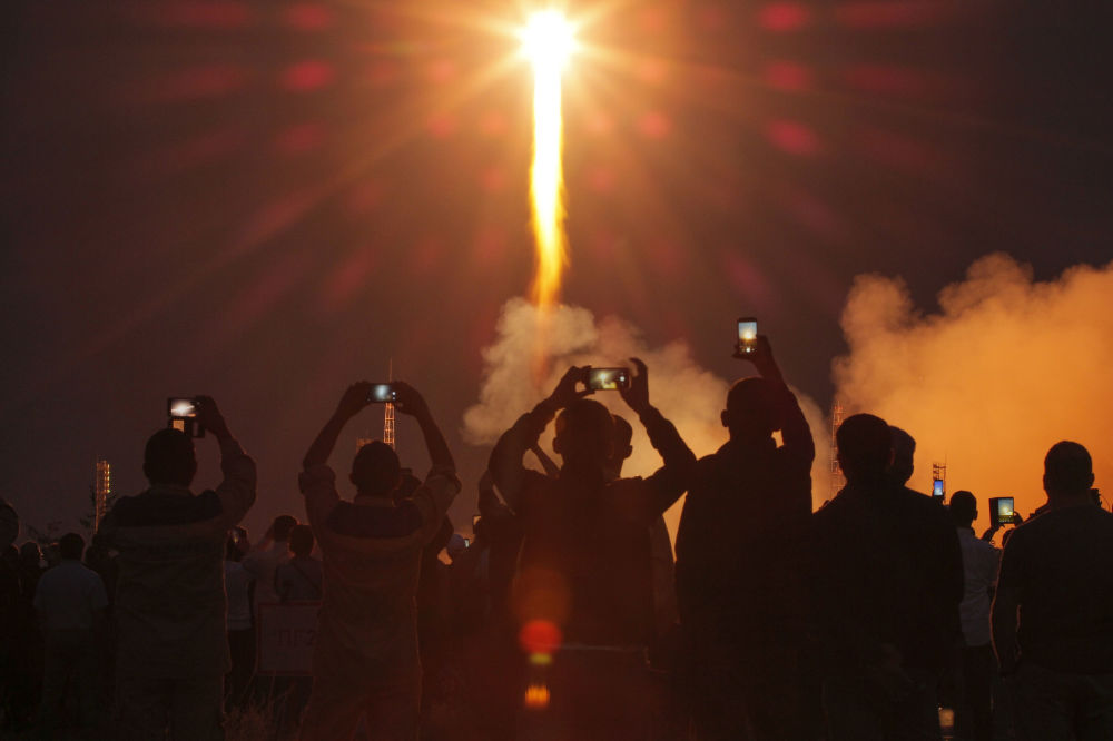 People watch the launch of the Soyuz-FG rocket booster with Soyuz MS-15 space ship carrying a new crew to the International Space Station, ISS, at the Russian leased Baikonur cosmodrome, Kazakhstan, Wednesday, Sept. 25, 2019. The Russian rocket carries U.S. astronaut Jessica Meir, Russian cosmonaut Oleg Skripochka, and United Arab Emirates astronaut Hazza Almansoori.