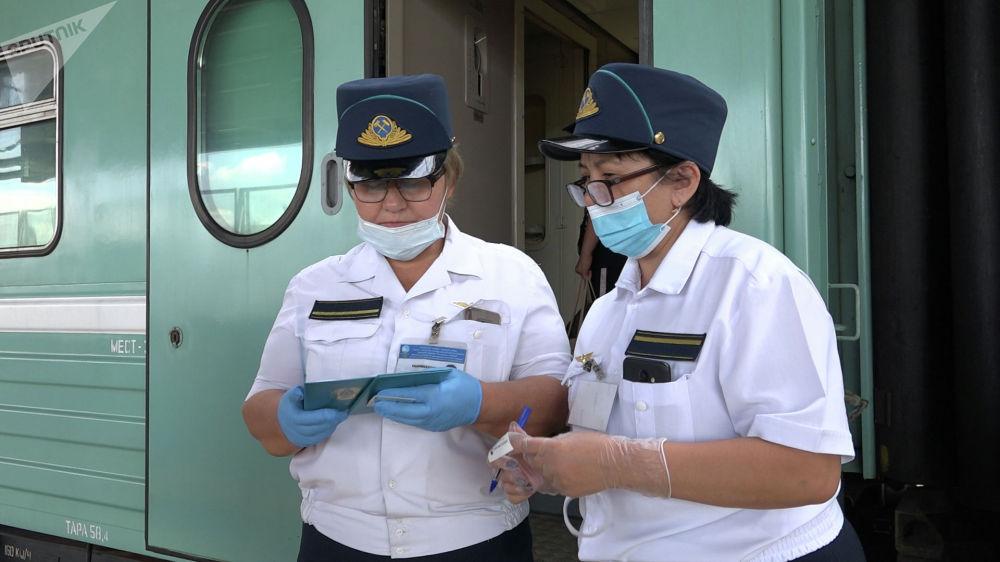 Проводники поезда на вокзале проверяют документы