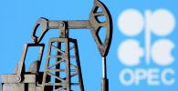 Модель нефтяной вышки на фоне логотипа ОПЕК