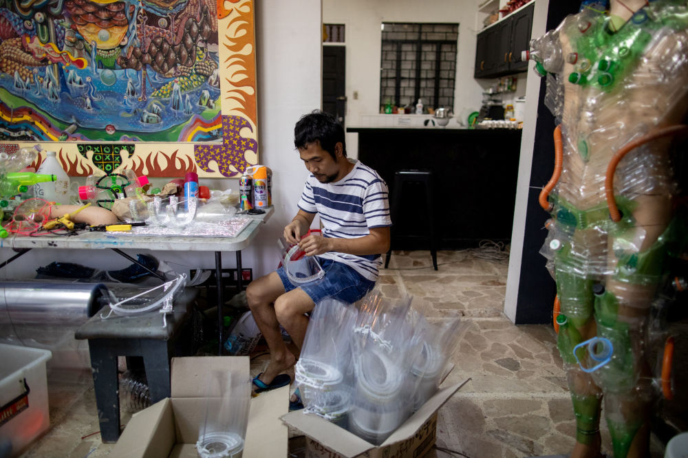 Jerial Pastor, studio assistant of Filipino artist Leeroy New, makes face shields for protection against the coronavirus disease (COVID-19) to be donated to healthworkers, in Quezon City, Metro Manila, Philippines, May 28, 2020.