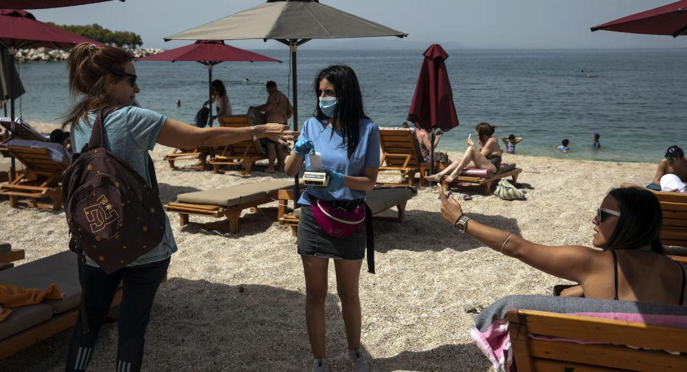 Посетительница оплачивает лежак на пляже в Афинах