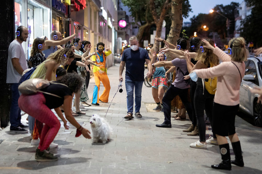 A man wears a mask and walks his dog past people taking part in a silent disco event as some businesses reopened at the end of last month under a host of new rules, following weeks of shutdown amid the coronavirus disease (COVID-19) crisis, in Tel Aviv, Israel June 4, 2020. Picture taken June 4, 2020.
