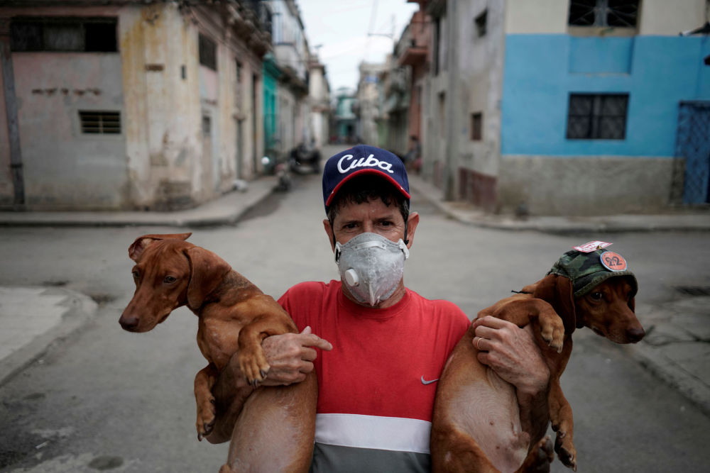 Roberto Gonzalez, who produces mini shows for tourists with his two Dachshunds, poses for a photo in front of his home amid concerns about the spread of the coronavirus disease (COVID-19), in downtown Havana, Cuba, May 18, 2020. Picture taken May 18, 2020.