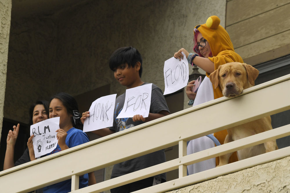 People and a dog watch from a balcony as demonstrators pass by during a protest, Saturday, June 6, 2020, in Simi Valley, Calif. over the death of George Floyd. Floyd died in police custody on Memorial Day in Minneapolis.