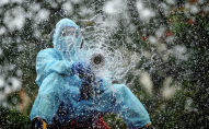Сотрудник коммунальных служб в защитной экипировке проводит дезинфекционную обработку на улице