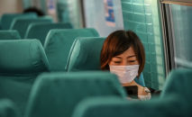 Девушка в маске в салоне самолета