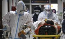 Врачи скорой помощи в защитных костюмах везут больного коронавирусом по коридору больницы