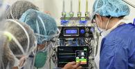 Медики настраивают аппаратуру в палате интенсивной терапии в больнице с коронавирусом