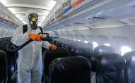 Сотрудник аэропорта проводит дезинфекцию салона самолета
