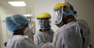 Врачи в защитных костюмах общаются в коридоре больницы с коронавирусом