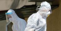 Медики в защитных костюмах у больницы с коронавирусом