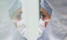 Сотрудница лаборатории в защитном костюме проводит исследования