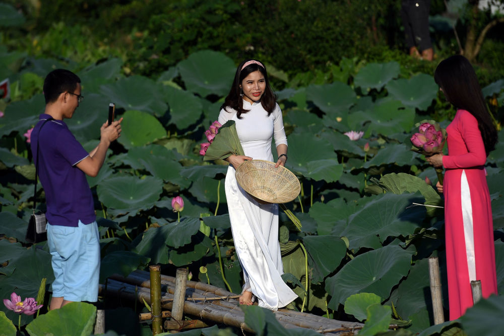 Women get their pictures taken during a photo shoot at the Westlake lotus ponds in Hanoi on June 13, 2020.