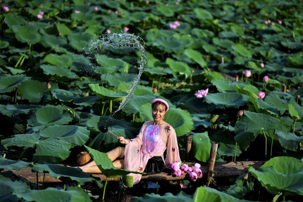 Девушка позирует на пруду с лотосами