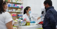 Люди покупают лекарства в аптеке