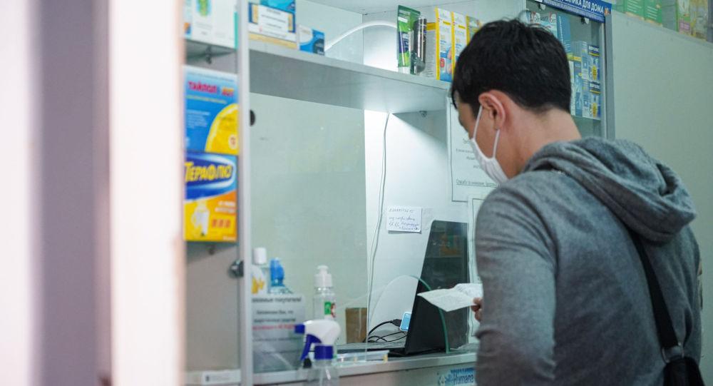 Мужчина в маске приобретает лекарства в аптеке
