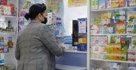 Женщина в маске покупает лекарства в аптеке