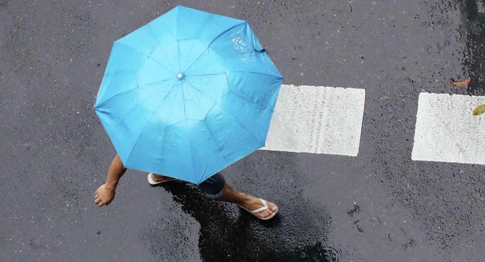 Девушка переходит улицу под дождем