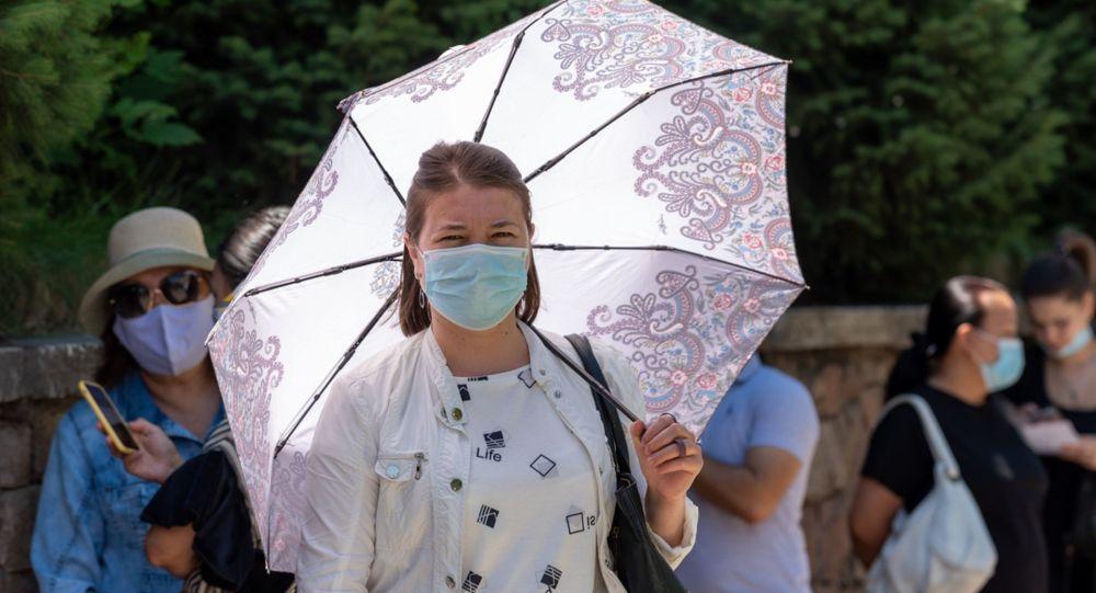 Женщина в маске под зонтом стоит в очереди перед центральной аптекой в Алматы