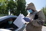 Полицейский в защитном костюме проверяет документы водителя