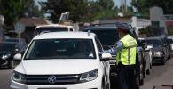 Полицейский в маске проверяет документы водителя