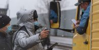 Полицейский  в маске под снегом проверяет документы у водителя грузовика