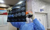 Медик в защитном костюме смотрит результаты МРТ в  больнице с коронавирусом