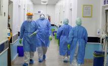 Медики в защитных костюмах в коридоре больницы с коронавирусом