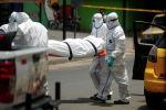 Работники больницы в защитных костюмах транспортируют тело погибшего от коронавируса
