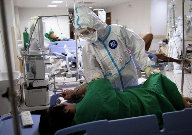 Медик в защитном костюме в палате больницы с коронавирусом