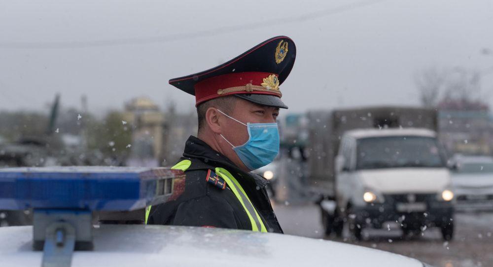 Полицейский в маске на блокпосту в снегопад, архивное фото